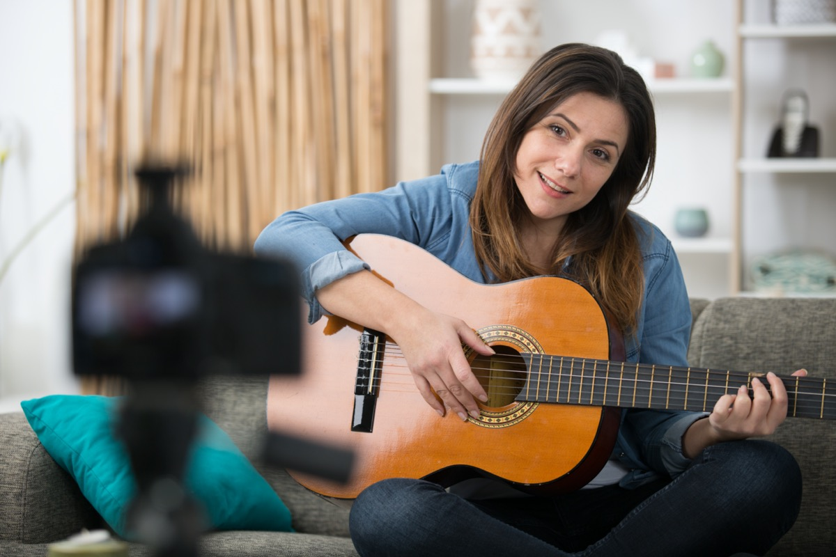 woman records a music blog with guitar