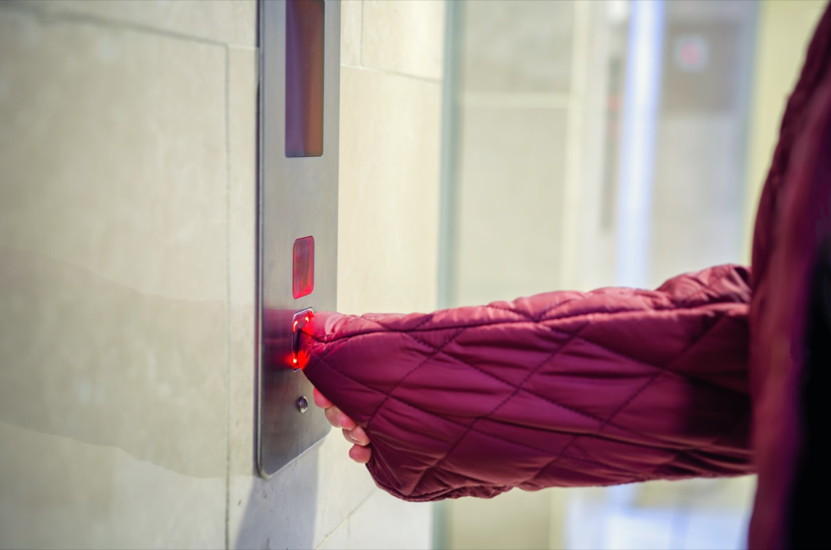 A woman pushing an elevator button with sleeve nylon down jacket instead of using her hand.