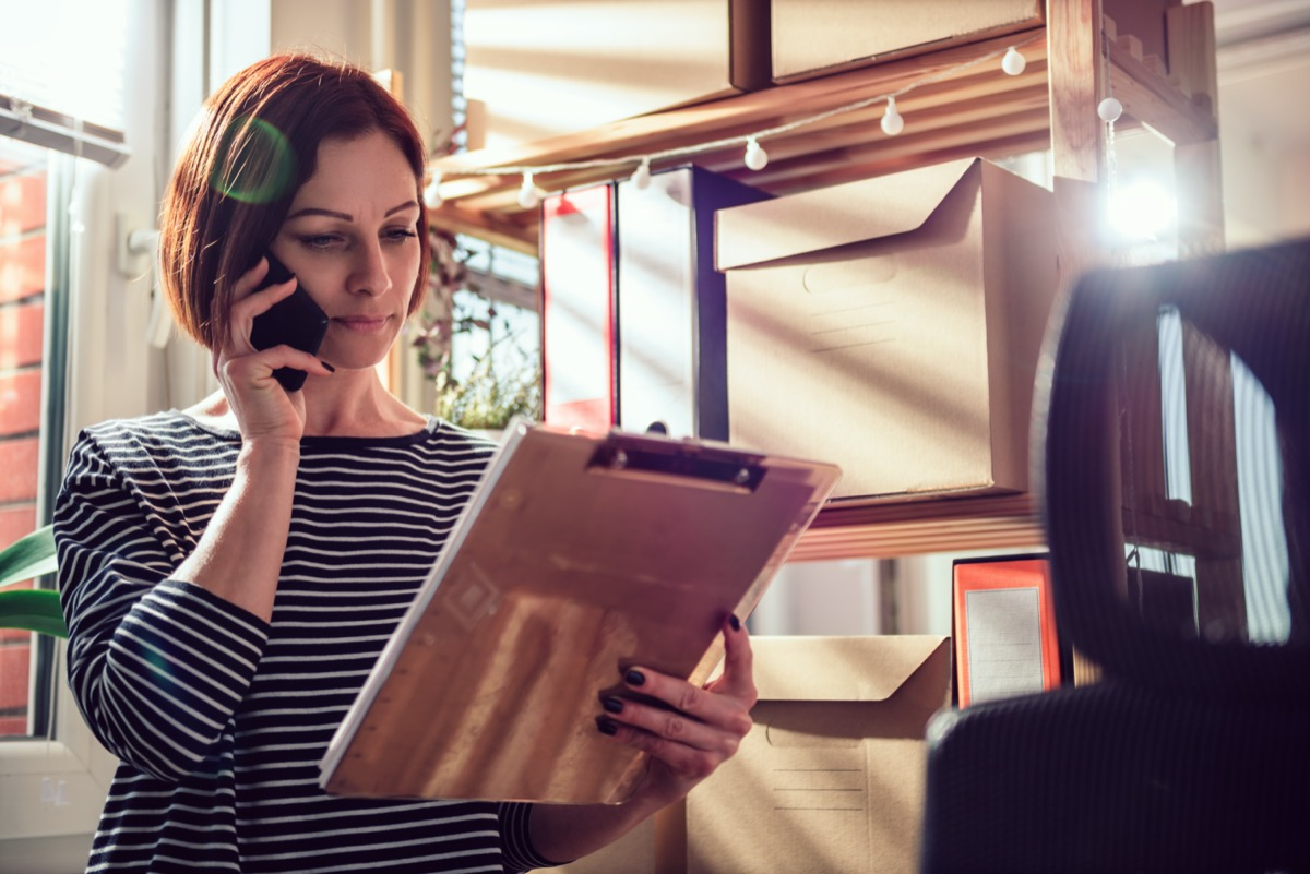Business woman wearing striped shirt talking on the phone at the office and looking at document