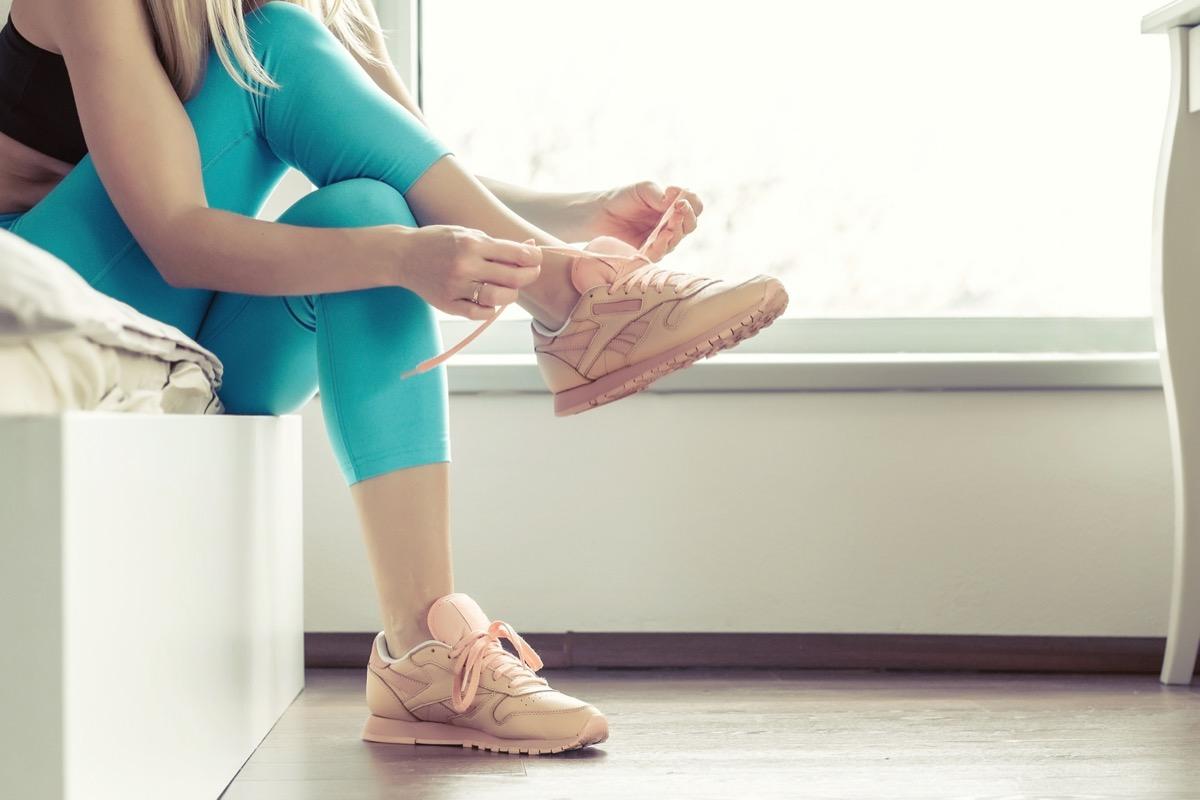 Fitness sport woman in fashion sportswear lacing sport footwear for running