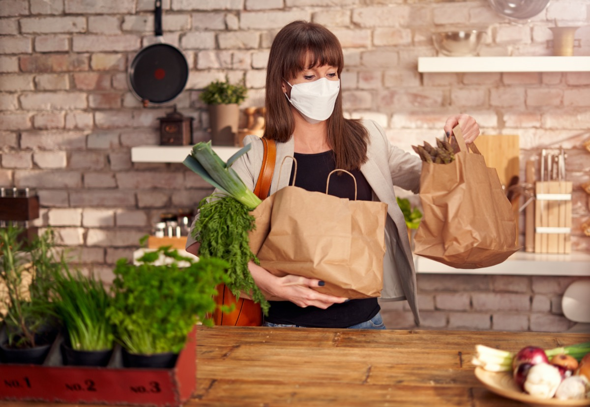 Woman wearing white medical face mask to prevent infection, arriving home, holding paper shopping bag. Protection against coronavirus
