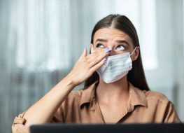 Don't Touch Your Face. Girl wearing surgical mask rubbing her eye with dirty hands, working on laptop