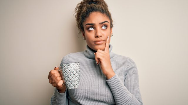 Woman wondering thinking cup