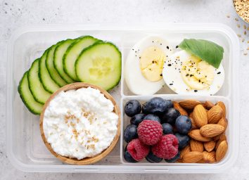 Breakfast bento box high protein with hard boiled eggs fruit nuts cottage cheese cucumber