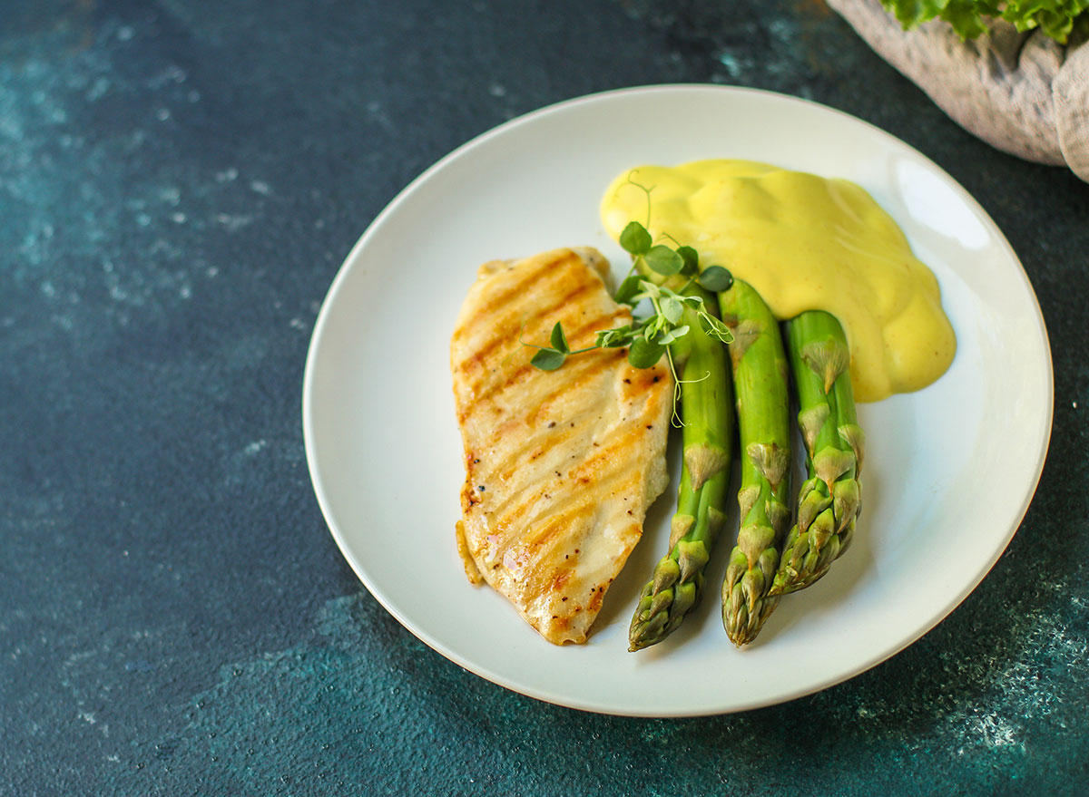 chicken hollandaise with asparagus on white plate