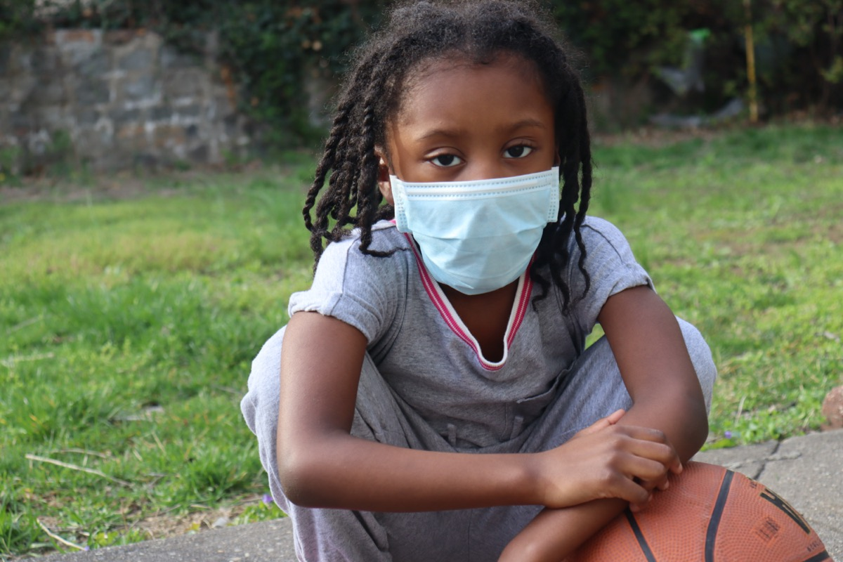 African American Kid wearing surgical mask with basketball