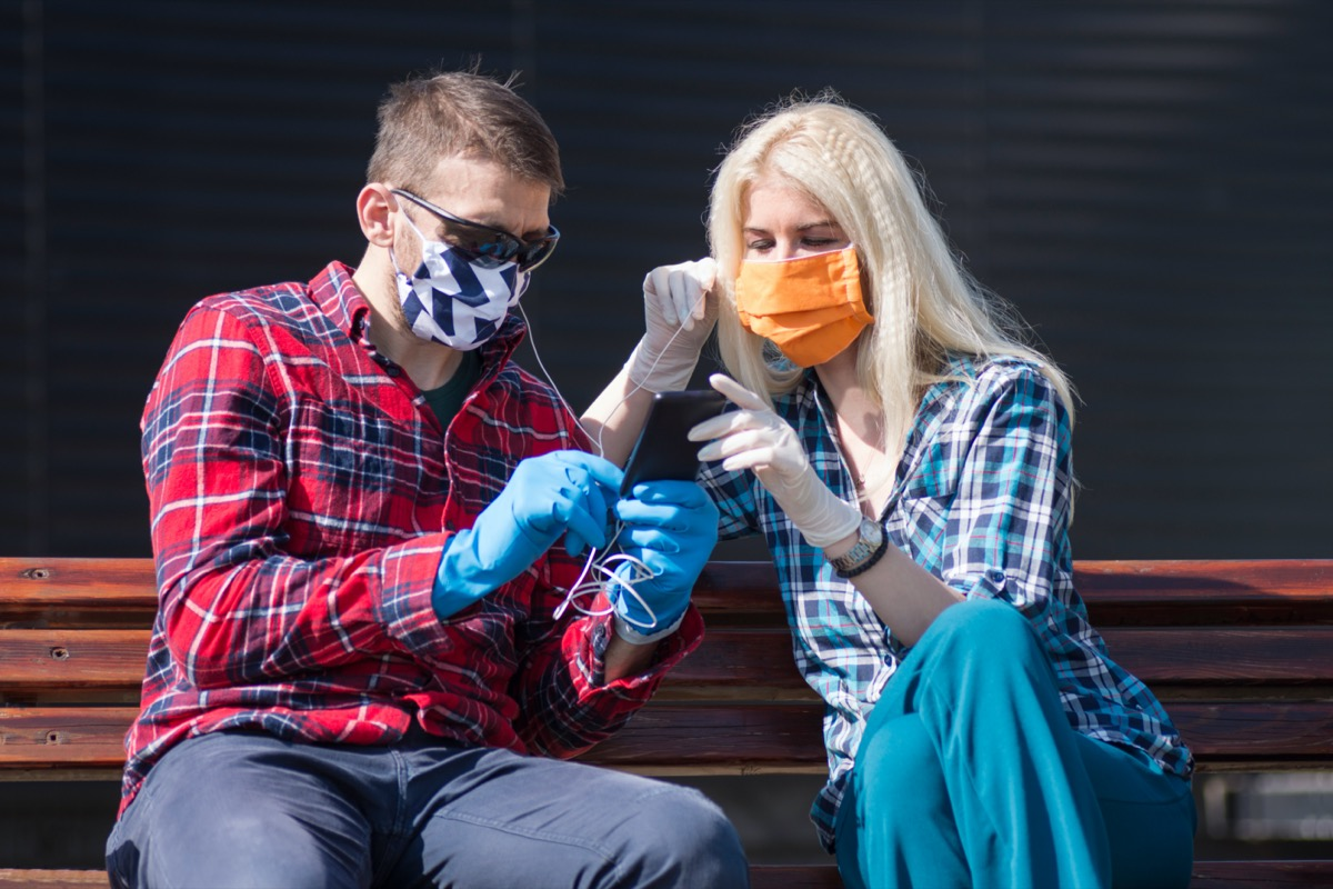 The couple with protective masks and gloves is listening music and using phone outdoors, modern lifestyle concept in coronavirus season.