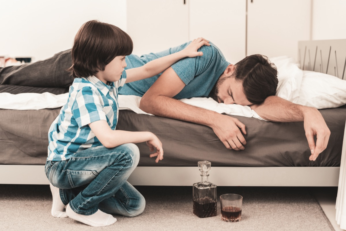 Little Boy Sitting in Room with Drunken Father
