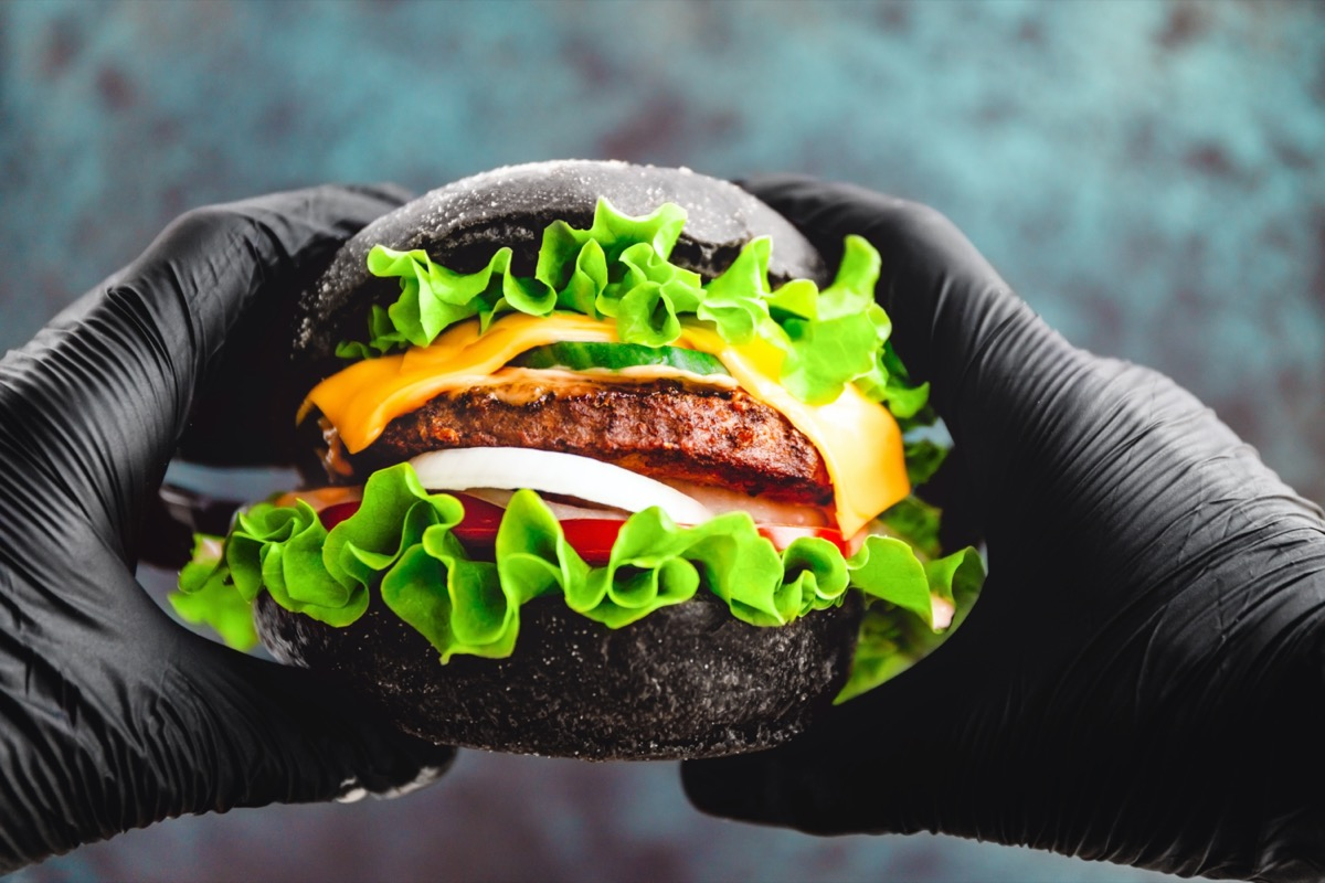 Hands in black gloves hold a big black burger with marble beef patty, cheese and fresh vegetables.