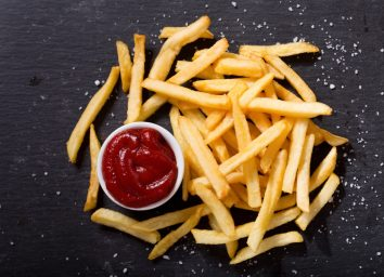 French fries with ketchup on dark background, top view