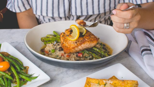 eating a bite of salmon with asparagus