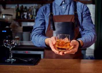 Hands of a bartender at bar restaurant with glass whiskey drink