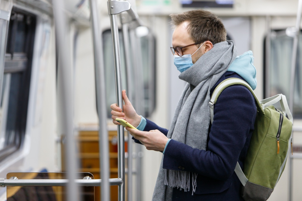 man in glasses feeling sick, wearing protective mask against transmissible infectious diseases and as protection against the flu in public transport/subway, using and looking at smartphone