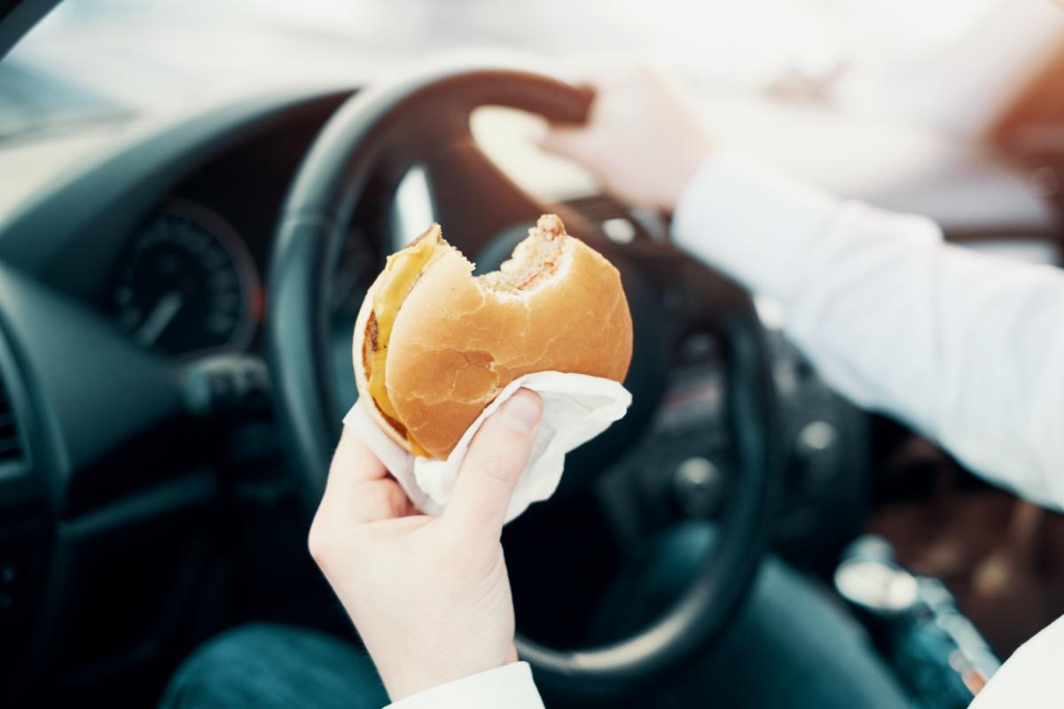 Man eating an hamburger and driving seated in his car