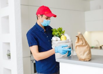 Man holding full bag of different healthy food on a wooden table in the home kitchen close up