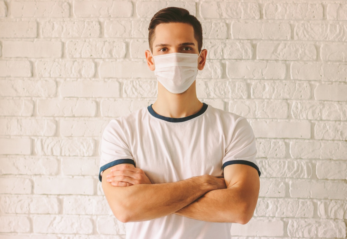 Portrait young confident man wearing face mask for protection against chinese coronavirus COVID-19