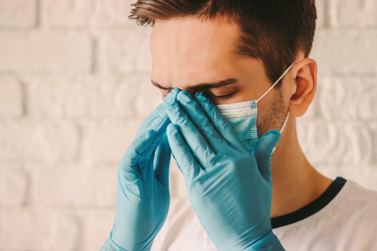 Frustrated tired man in protective gloves on hands and medical face mask feeling headache.