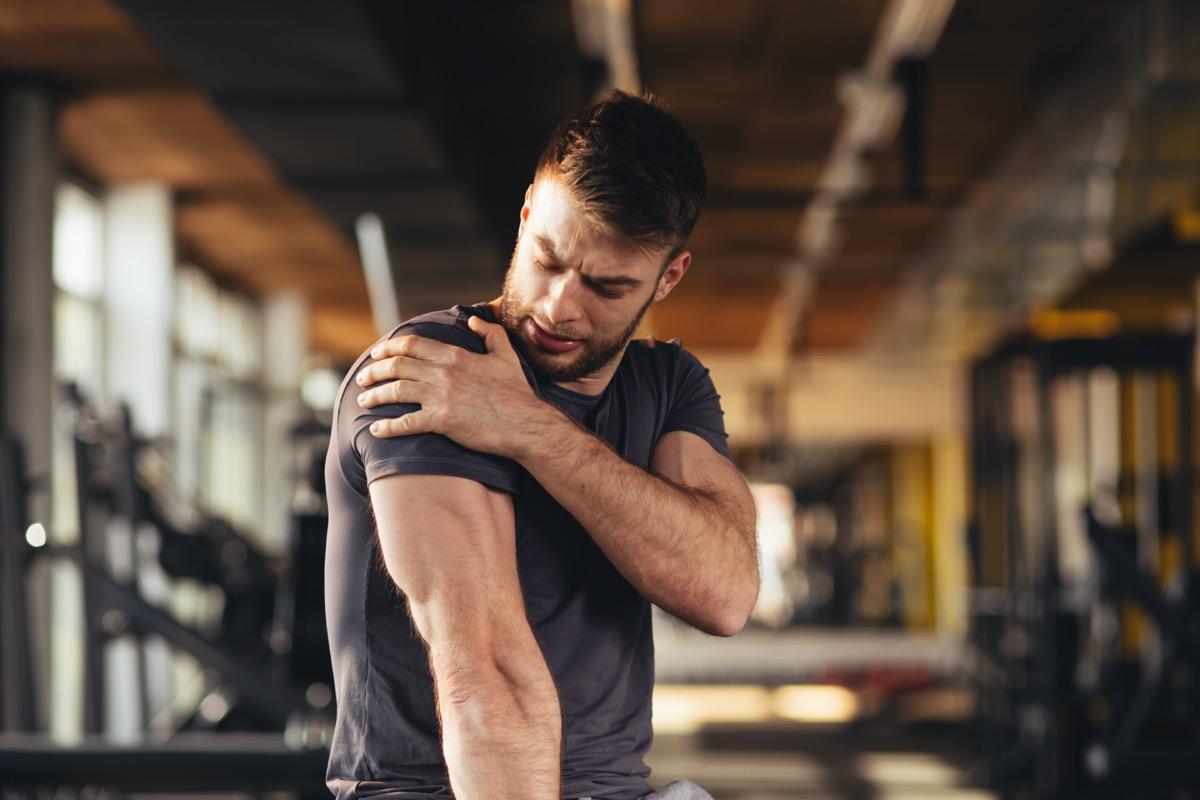 man feeling the pain in shoulder at the gym