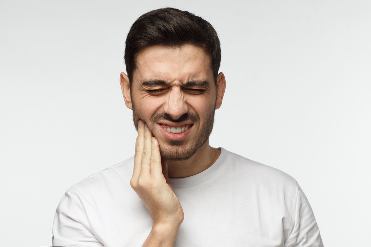 man isolated on gray background touching his face and closing eyes with expression of horrible suffer from health problem and aching tooth, showing dissatisfaction