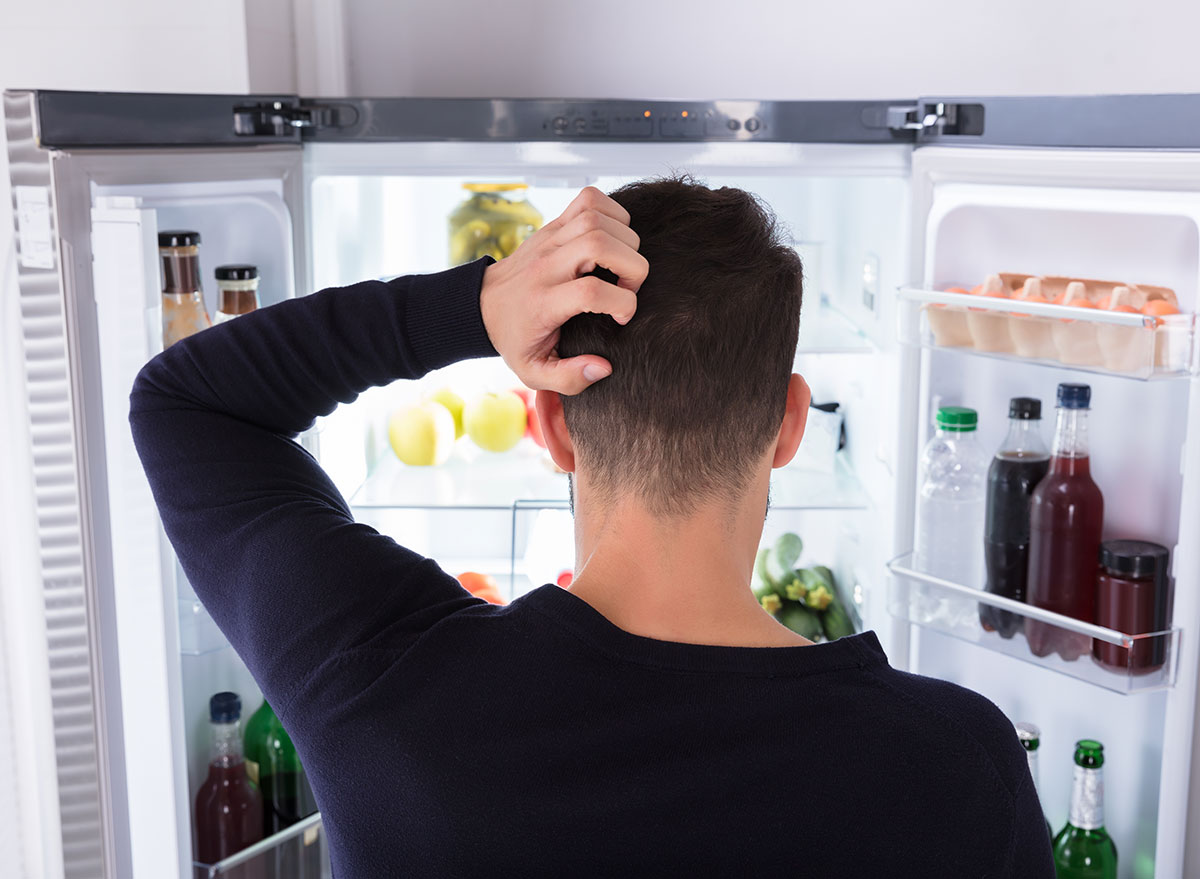 man looking in fridge