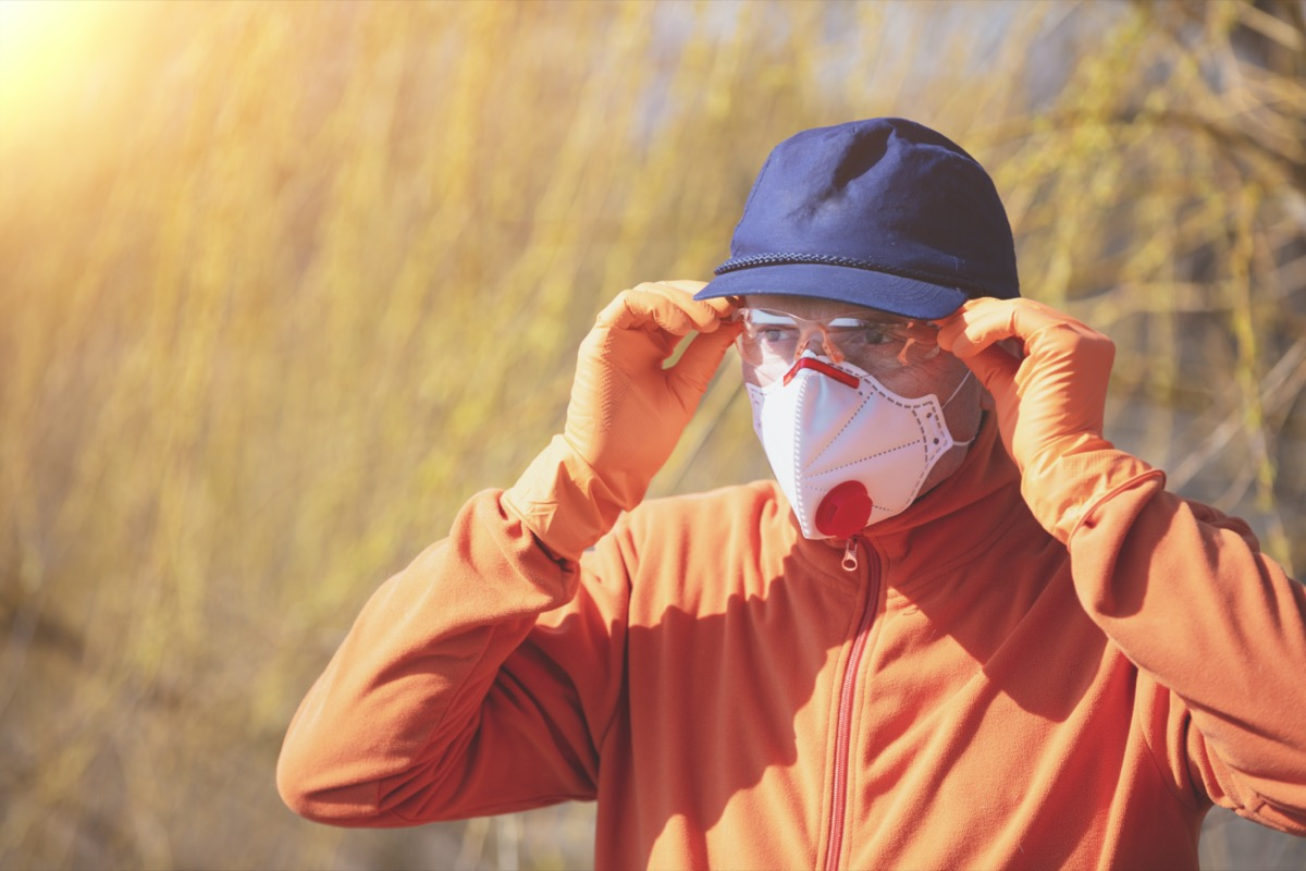 A man in medical face mask (respirator) and safety glasses outdoors