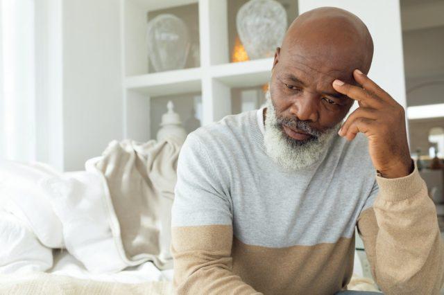senior African American man sitting on white sofa in light room in beach house