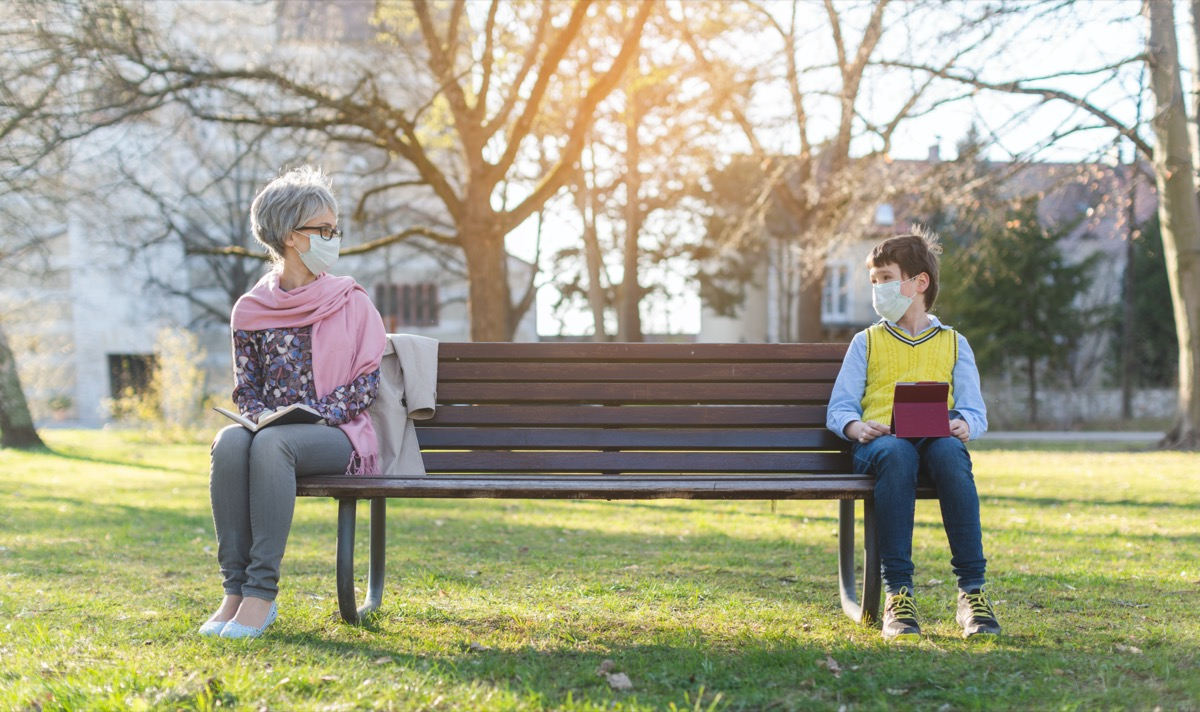 Grandmother and grandson separated by social distancing on park bench