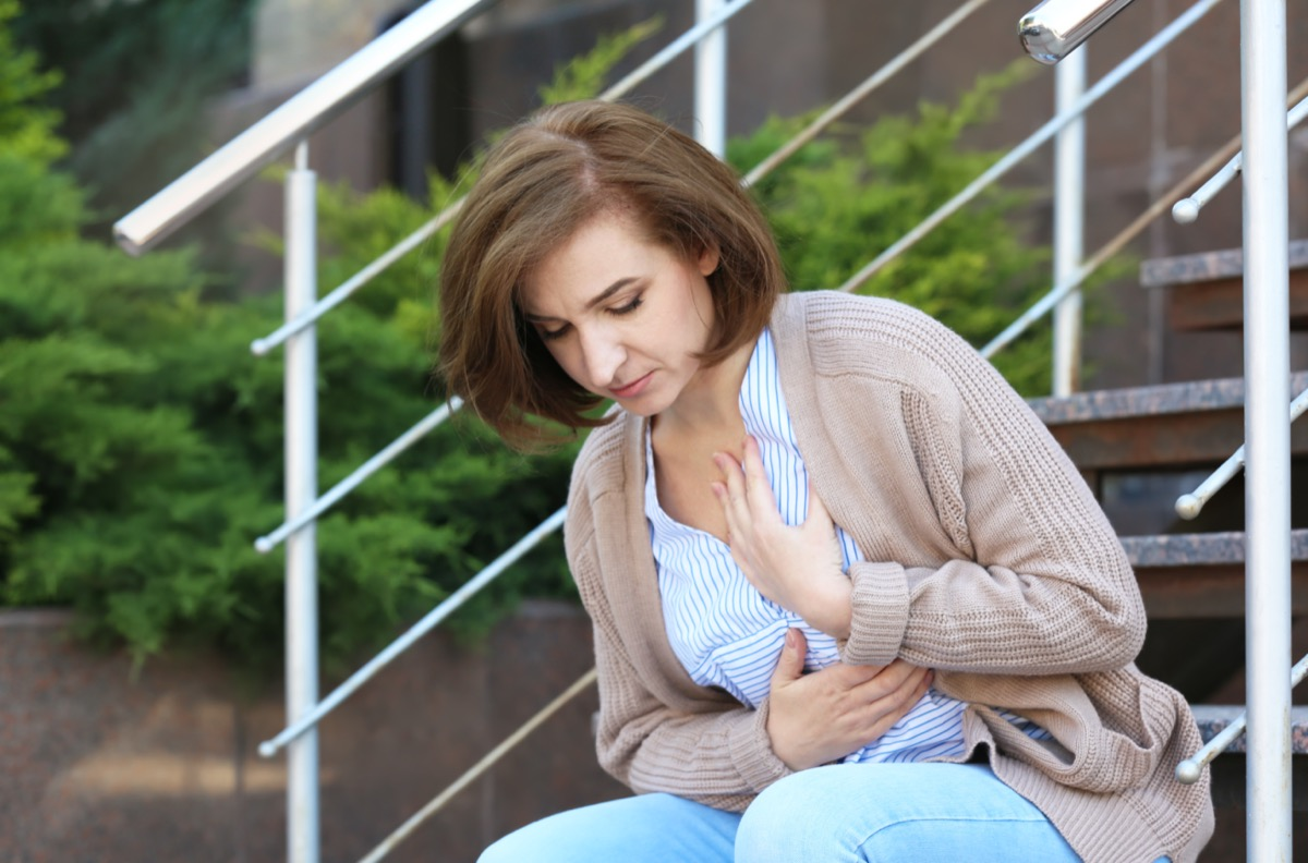 Mature woman having heart attack on stairs, outdoors