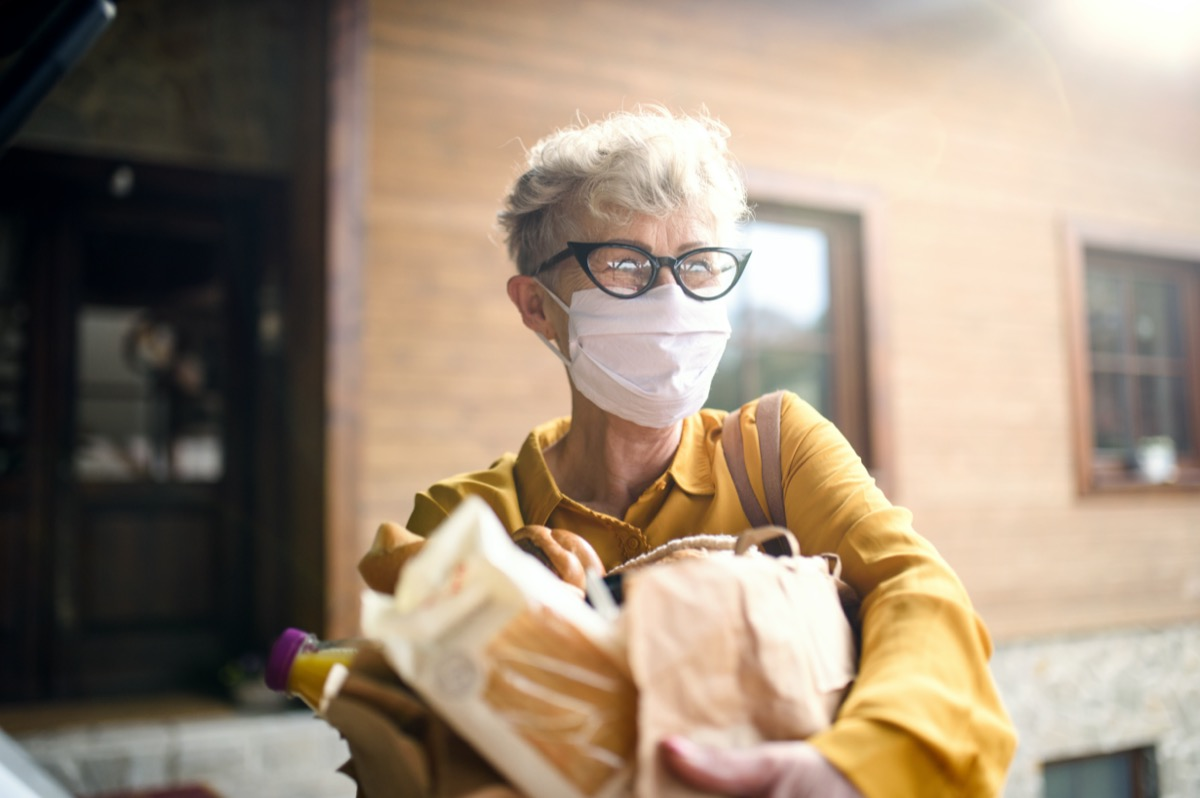 Senior woman with face mask outdoors with shopping, corona virus and quarantine concept.
