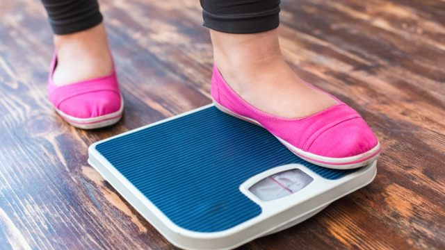 woman stepping on scale in pink flats
