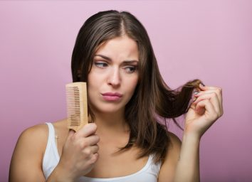 Woman brushing her hair with a wooden comb