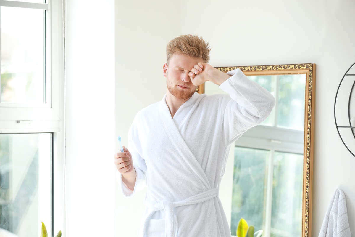 Morning of sleepy young man with toothbrush in bathroom