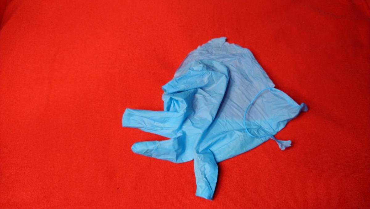 Broken medical glove on red background