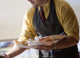 Waiter clearing table at restaurant