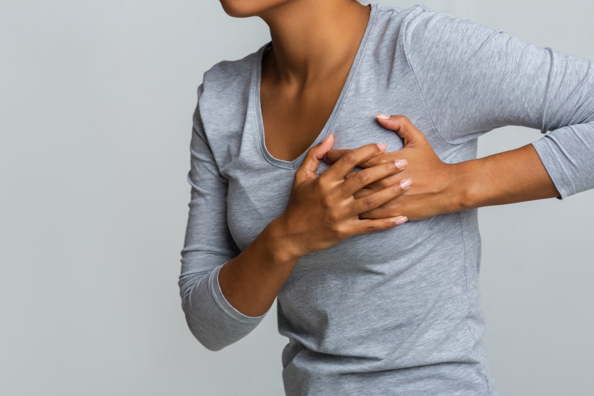 african woman feeling menstrual cyclic breast pain, touching her chest,