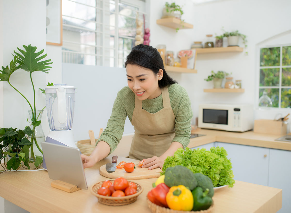 woman cooking with recipe on ipad