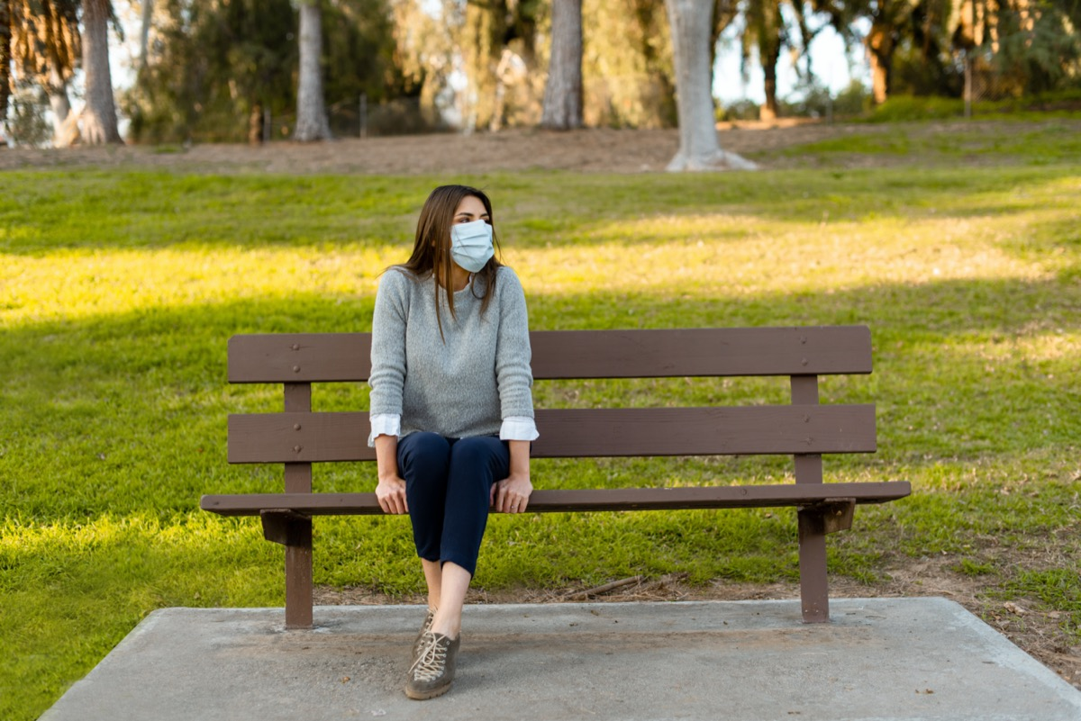 woman outdoor wearing medical face mask, social distancing, sitting on a bench, isolated from other people