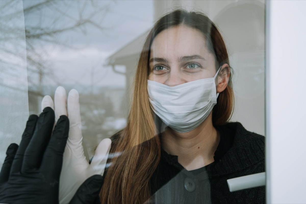 happy woman seeing her fried who came to visit her due to coronavirus covid-19 wit mask and gloves on window at home