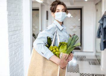 Young woman in medical mask coming home with shopping bag full of fresh food.