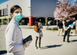 Shopper with mask standing in line to buy groceries due to coronavirus pandemic in grocery store