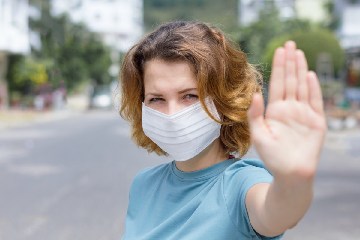 woman in protective sterile medical mask on her face looking at camera outdoors, on asian street show palm, hand, stop no sign