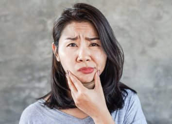 woman having problem with Bell's Palsy/Facial Palsy, hand holding her face