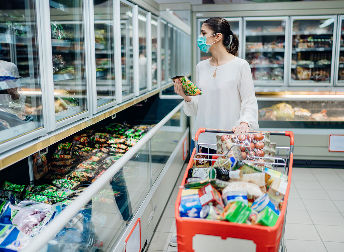 woman grocery shopping with mask