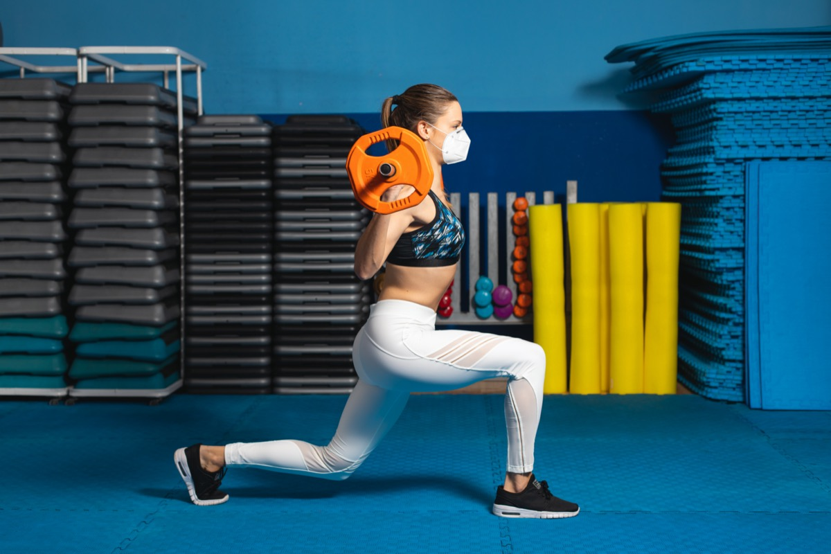 woman doing lunges at the gym wearing n95 face mask