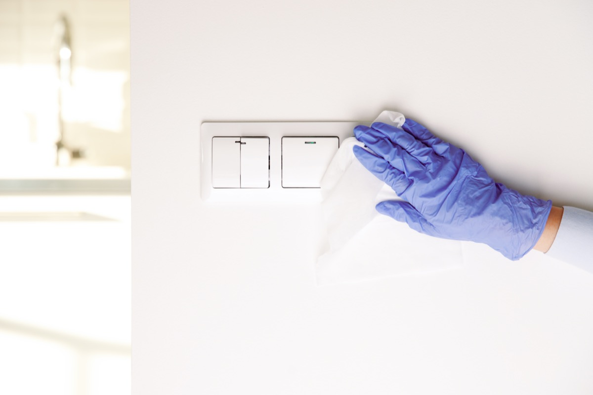 female hands in blue latex gloves, cleaning light switches with towel