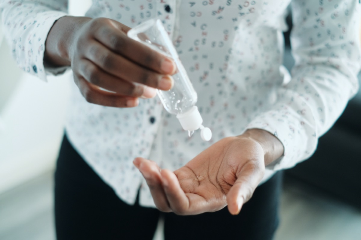African American Woman Disinfecting Skin With Hand Sanitizer
