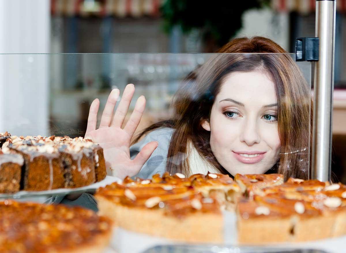 woman looking into bakery window