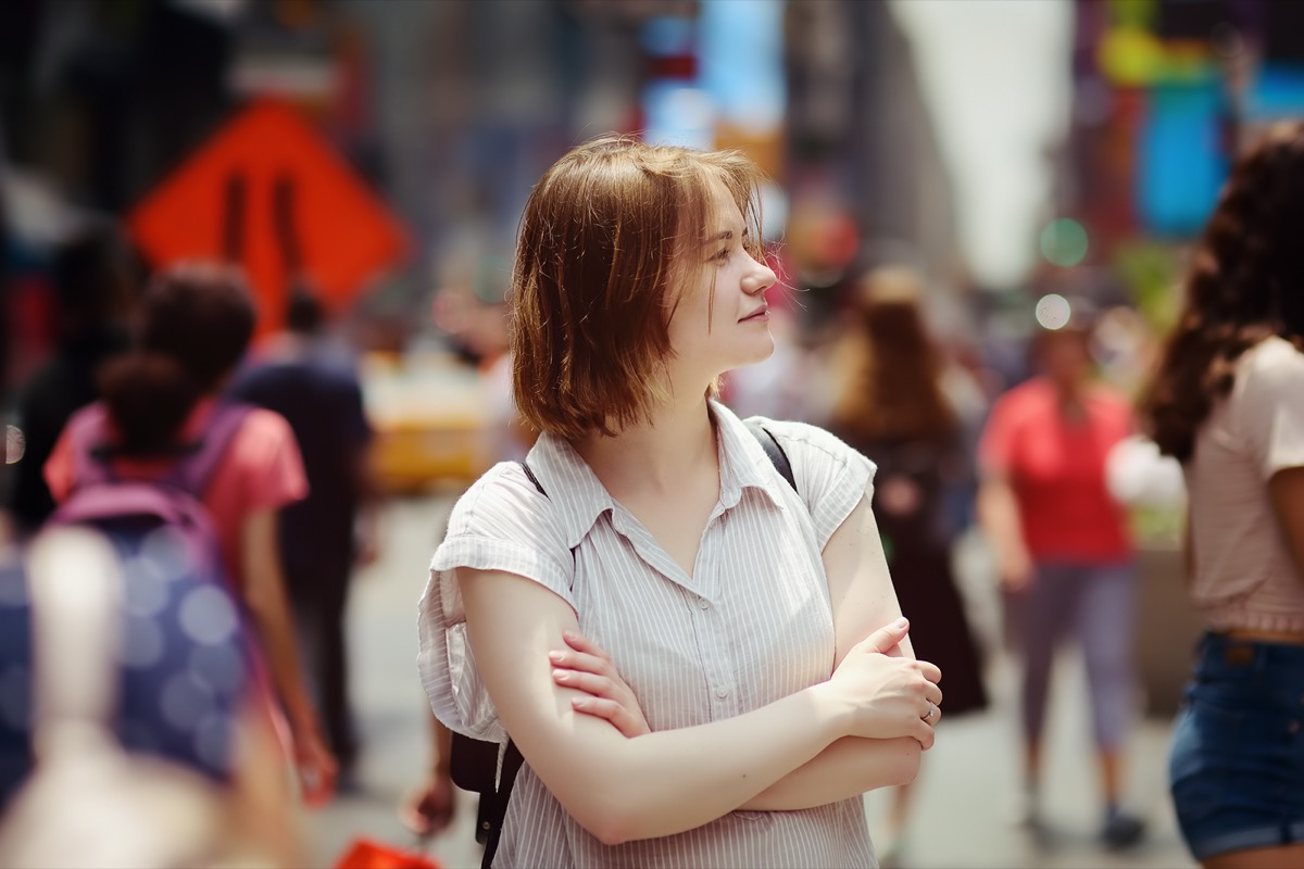 Charming young woman tourist looking on Times Square on sunny summer day, downtown Manhattan