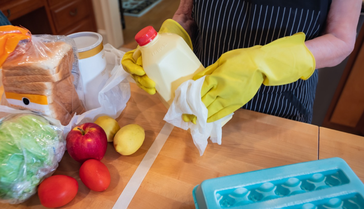 Woman wearing gloves and using disinfectant sanitizing wipes to clean grocery items to prevent the spread of the COVID-19 virus