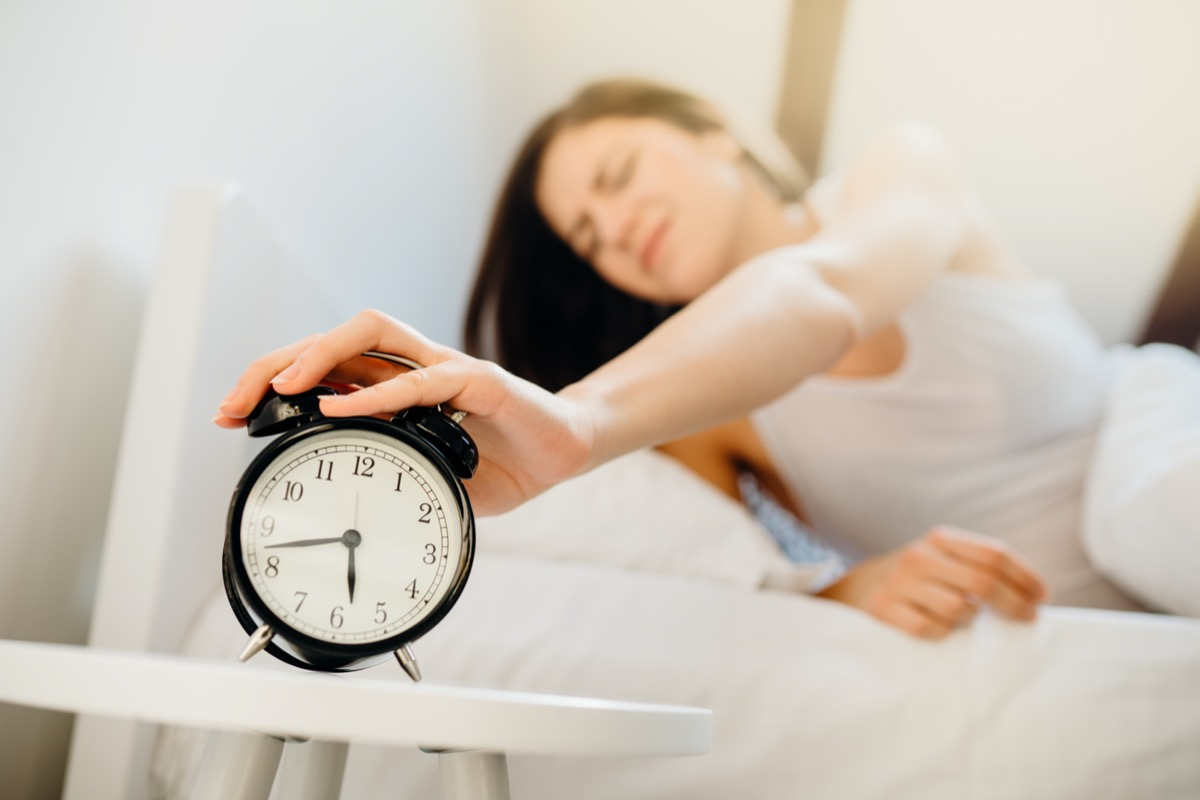 Alarm clock ringing,annoyed woman waking up in early morning for work.Sleeping disorder